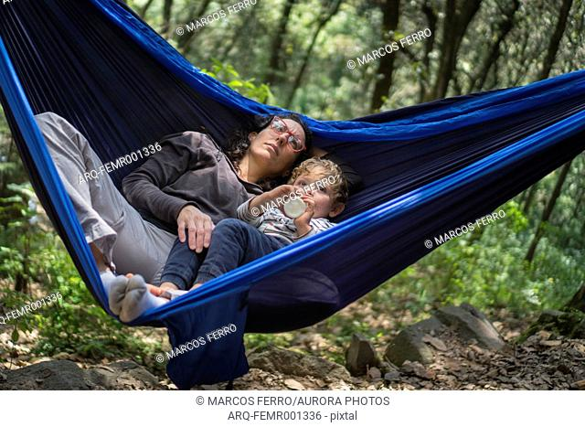 Mother and son snuggling in hammock, Mexico