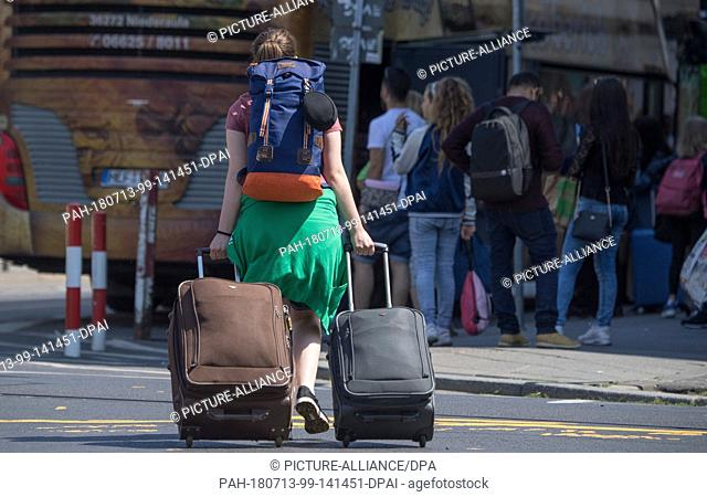 13 July 2018, Germany, Frankfurt: A woman pulling her suitcases to a waiting bus. There are constant chaotic transport scences at the bus parking area on the...