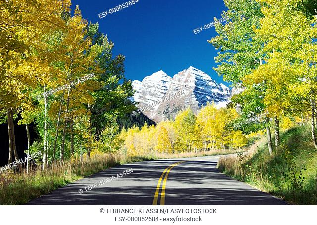 Roadway, fall foliage and the Maroon Bells in Colorado, USA
