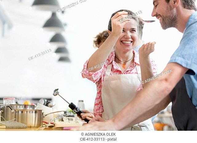 Smiling couple tasting food in cooking class kitchen