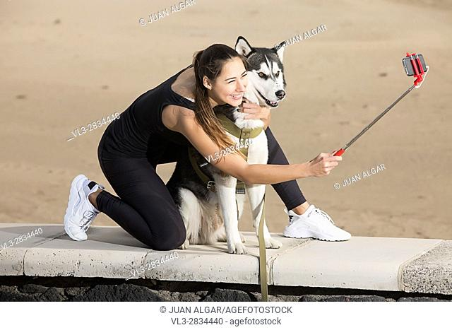 Smiling woman doing selfie with husky