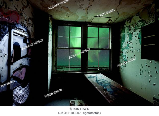 View of northern lights out a window in an abandoned building (digital composite/illustration)