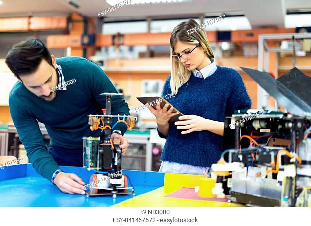 Young attractive students of mechatronics working on project together