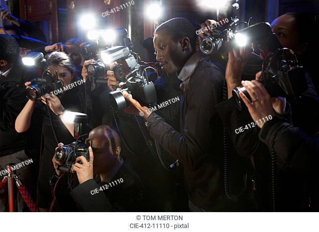 Paparazzi using flash photography at red carpet event