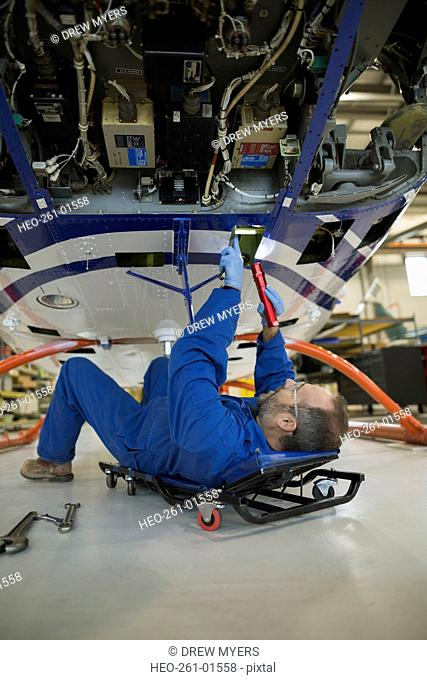 Mechanic working underneath helicopter