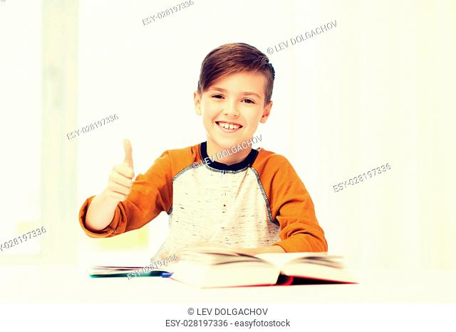 education, childhood, people and school concept - happy student boy with textbook and notebook showing thumbs up at home
