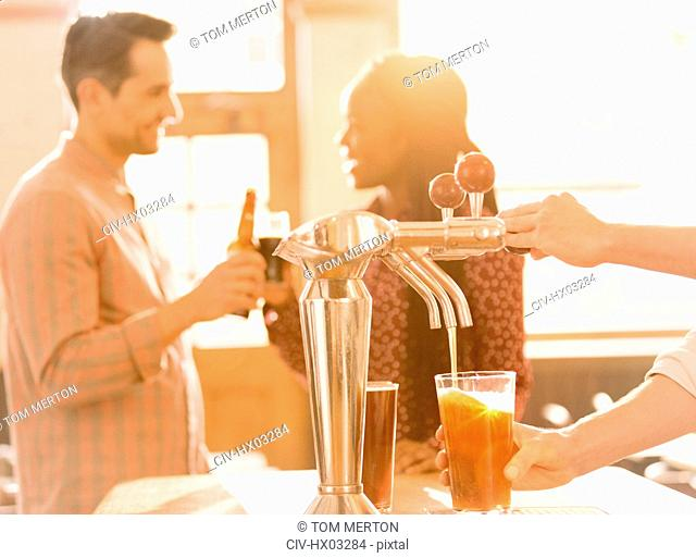 Couple drinking beer behind bartender pouring beer at beer tap in bar