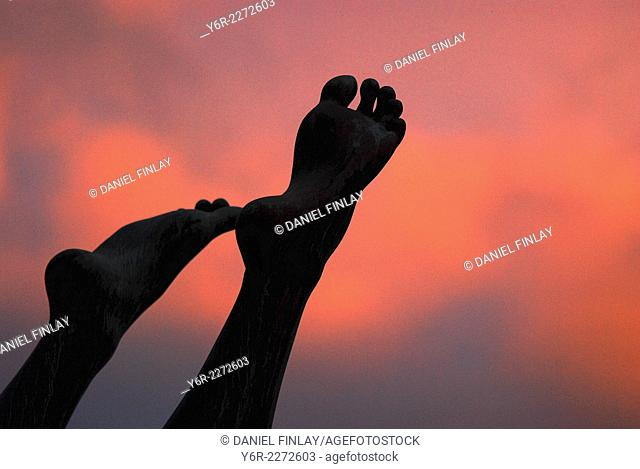 Feet of Diving Girl statue seen against a sunset sky near Tower Bridge in the heart of London, England