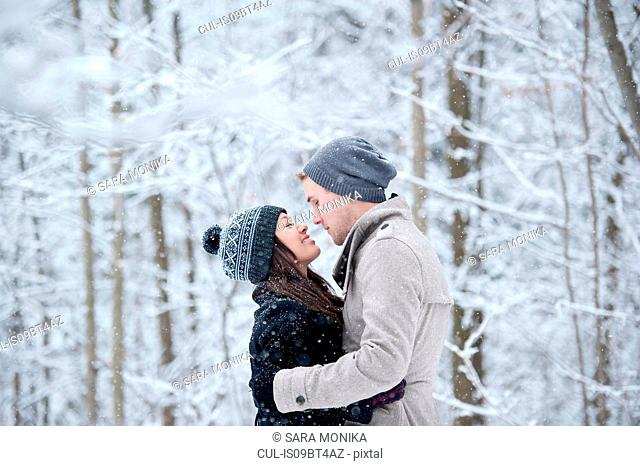 Romantic young couple face to face in snowy forest, Ontario, Canada