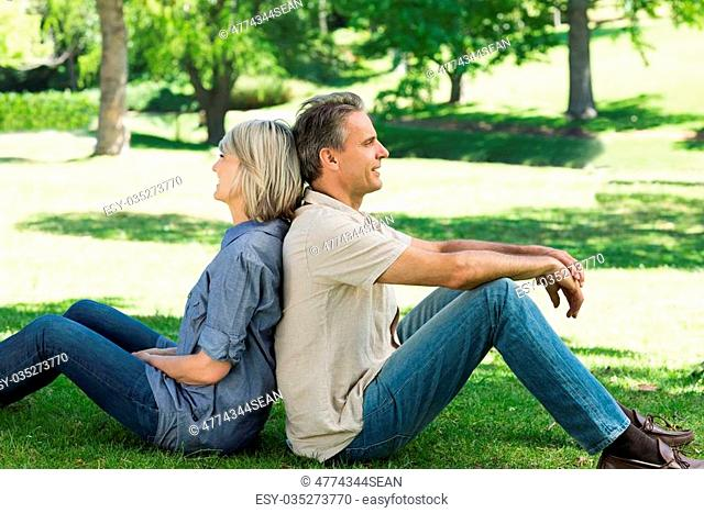 Side view of happy couple sitting back to back in a park