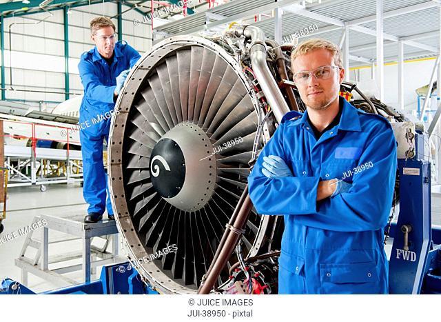 Portrait of confident engineer standing next to engine of passenger jet in hangar