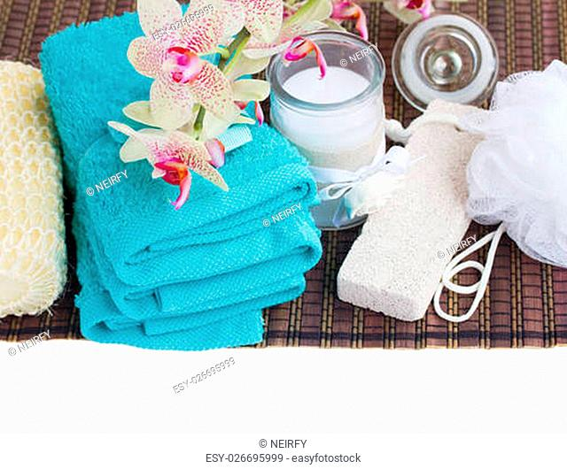 spa setting with towels, aroma candle and bath accessories on white