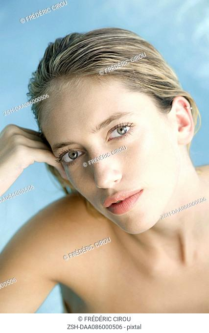 Young woman relaxing in pool, portrait