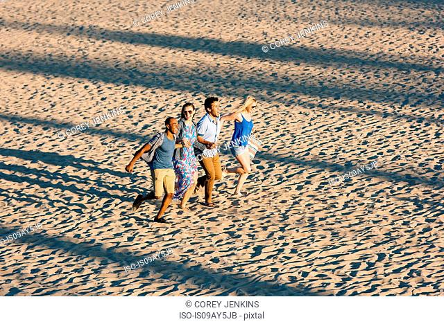 Four adult friends holding hands and running on beach, Santa Monica, California, USA