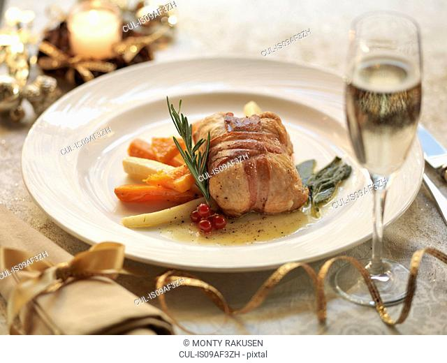Turkey parcel wrapped in pancetta, stuffed with cranberry and orange and served with lemon and sage sauce with roasted winter vegetables