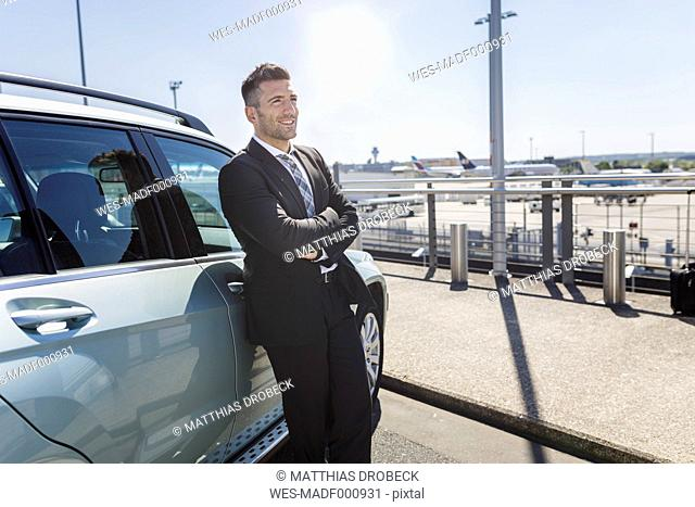 Businessman leaning against car at the airport
