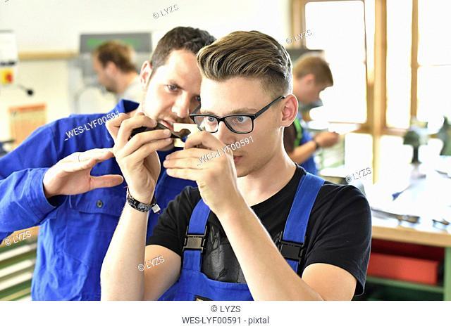 Instructor examining workpiece of trainee