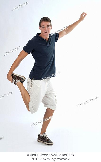 Full-body photograph of a teenage boy standing with a jump or making a pirouette
