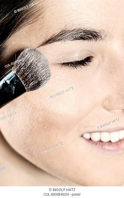 Close up of face powder being applied near young woman's eye