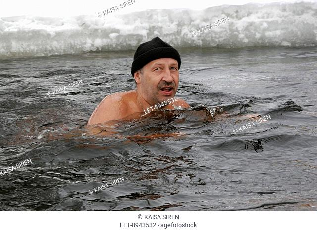 Outdoor winter swimming. Swimming in a hole made through ice