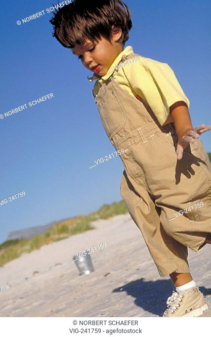beachscene, full-figure, 6-year-old boy wearing yellow shirt, beige trousers and gym shoes walking in the sand  - GERMANY, 08/08/2004