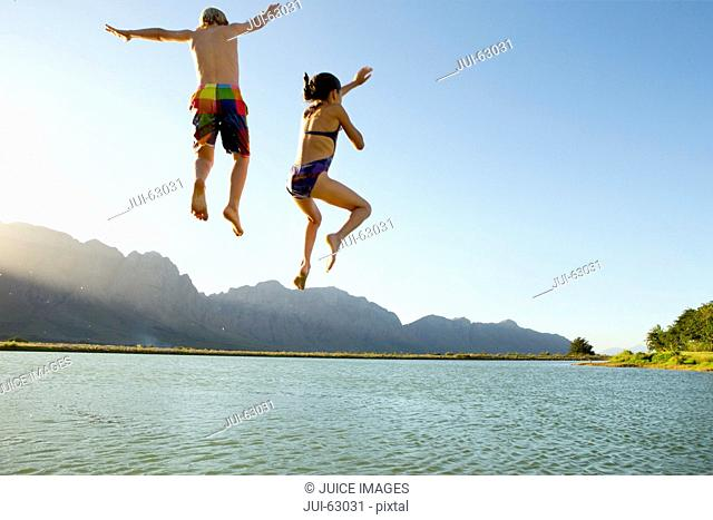 Children in swimwear, jumping into a lake from a jetty