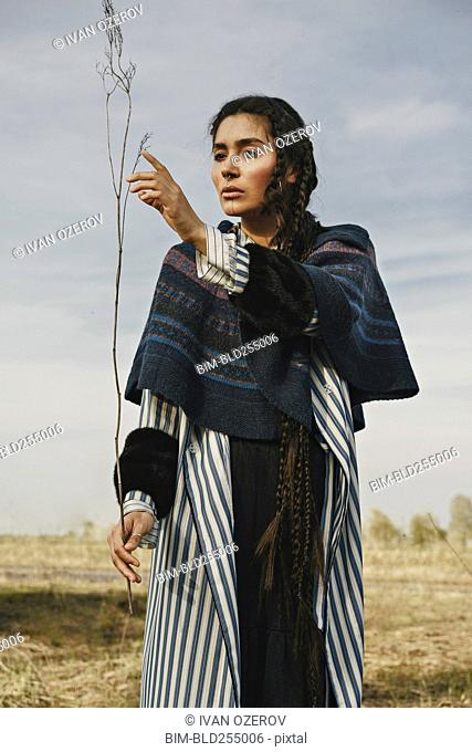 Caucasian woman wearing traditional clothing examining twig