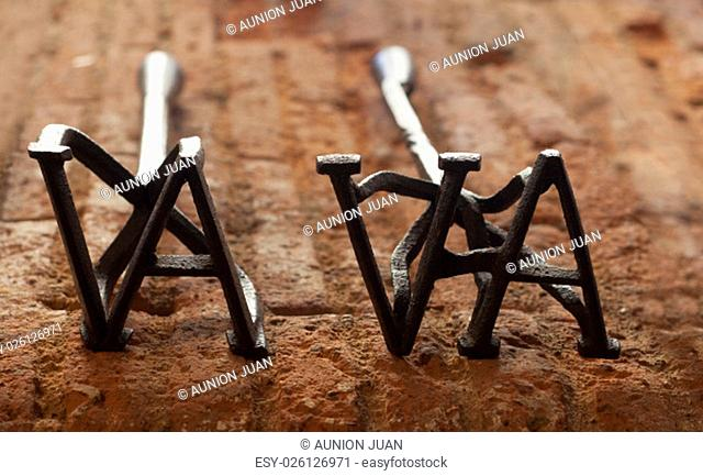 Two branding irons for cattle over weathered red bricks