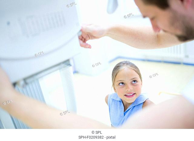 Doctor preparing girl for x-ray in hospital