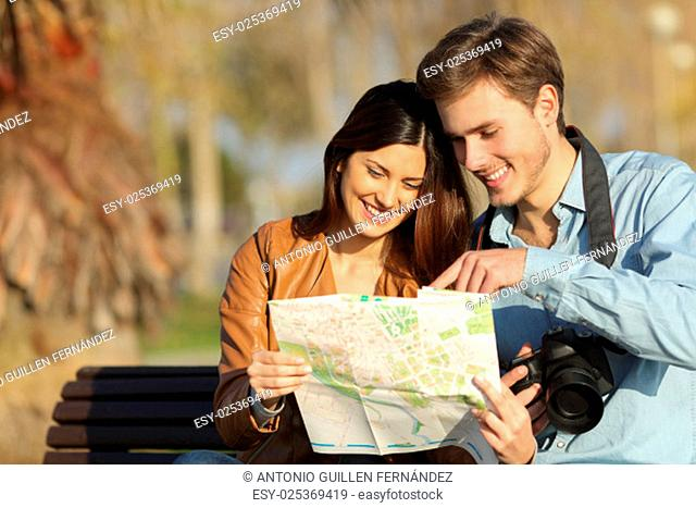 Happy tourists searching landmarks in a map sitting on a bench outdoors