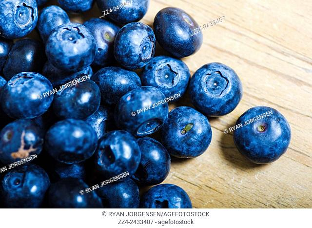 Horizontal food photography on a blue berry pile placed on wood surface