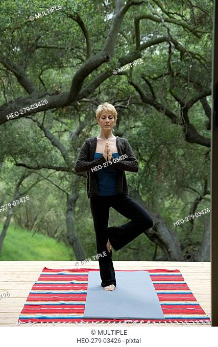 Serene woman practicing yoga tree pose on deck