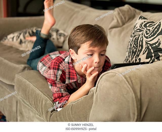 Boy playing with digital tablet on sofa