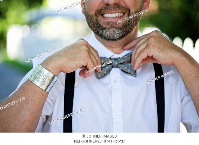 Man adjusting bow tie