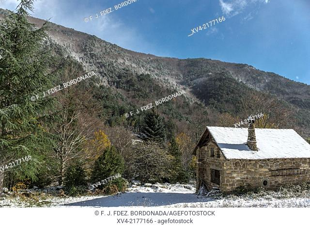 Traditional rural architecture of Pyrenees snow-covered in Hecho Valley, Huesca Pyrenees, Aragón, Spain