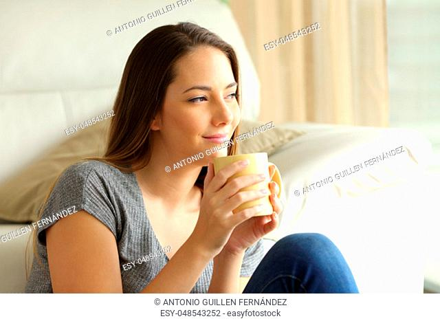 Relaxed girl sitting on the floor thinking with a cup of coffee looking through a window in the living room at home