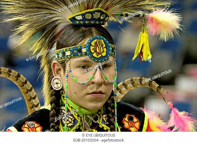 International Peace Pow Wow Head shot of Blackfoot Indian dancer with feather headdress bead work headband and string of beads across face