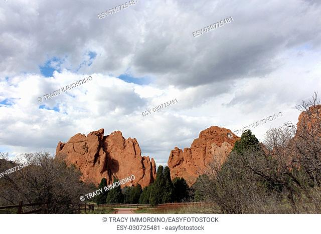 A trail leading to red rock formations rising behind pine trees at the Garden of the Gods in Colorado Springs, Colorado, USA, under cloudy skies
