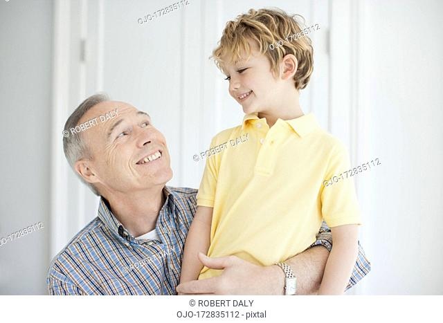 Smiling grandfather and grandson hugging