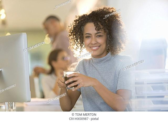 Portrait smiling businesswoman drinking coffee in office