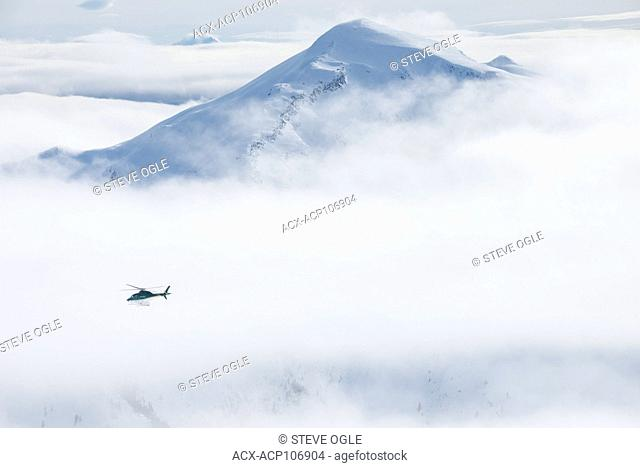 An A-Star helicopter flies past a remote mountain peak Northern Escapes heli-skiing near Terrace, British Columbia
