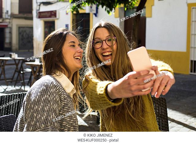 Laughing young woman taking a selfie with her friend at street cafe