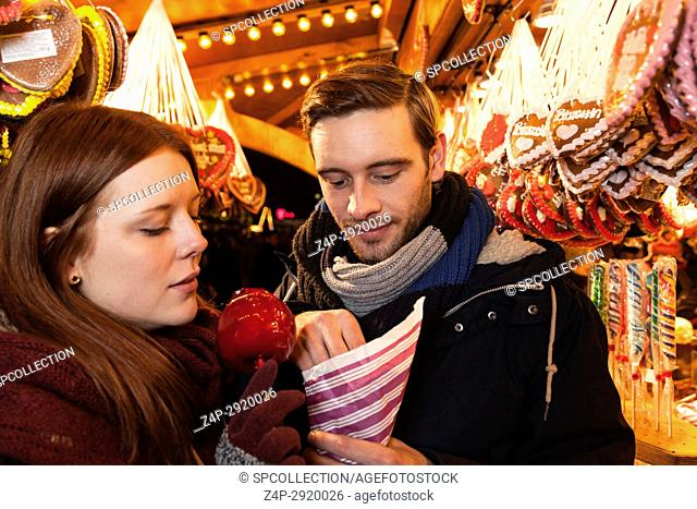 couple with sweets on christmas market
