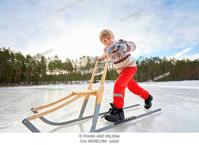 Boy pushing kicksled across frozen lake, Gavle, Sweden
