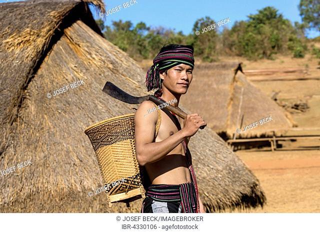 Man in traditional costume in front of a Phnong house, ethnic minority, Pnong, Bunong, Senmonorom, Sen Monorom, Mondulkiri Province, Cambodia