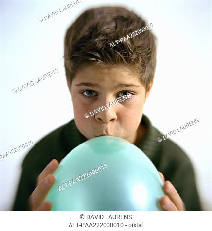 Boy blowing up balloon, portrait