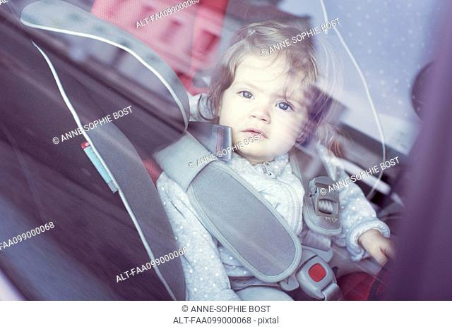 Baby girl sitting in car seat, gazing through car window