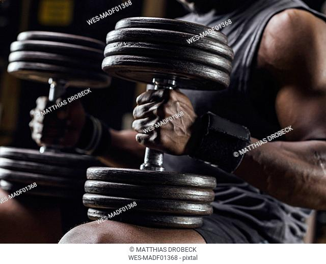 Athlete traing with dumbbells in gym, close up