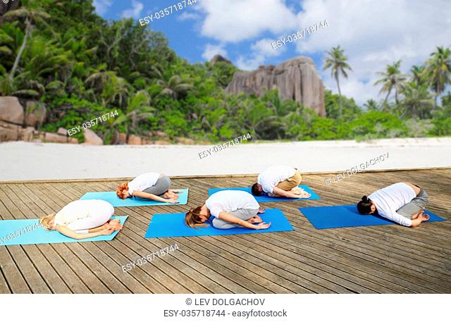 fitness, sport, yoga and healthy lifestyle concept - group of people making child pose over tropical beach background
