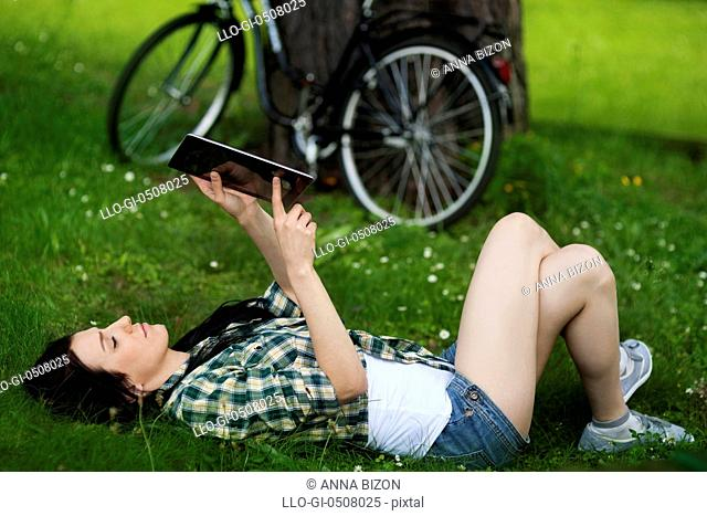Beautiful young woman using digital tablet outdoors, Debica, Poland